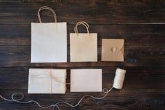 Contenitore di regalo del cartone di Kraft del modello e pacchetto della maniglia su fondo di legno per il fondo del sito Web di  Immagini Stock
