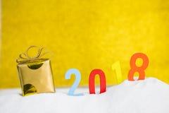 Contenitore di regalo del nuovo anno con testo di legno sulla sabbia bianca sopra il fondo vago dell'oro Fotografia Stock