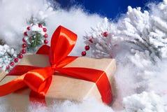Contenitore di regalo del primo piano con l'arco rosso ed il fondo blu fotografia stock libera da diritti