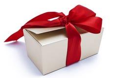 Contenitore di regalo dell'oro con il nastro rosso Immagini Stock