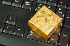 Contenitore di regalo dell'oro sulla tastiera di computer nel concetto online di acquisto Fotografie Stock