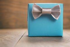 Contenitore di regalo della carta blu con l'arco d'argento del nastro sulla tavola di quercia Immagine Stock