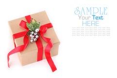 Contenitore di regalo della carta di Brown con l'arco rosso del nastro, isolato su bianco Fotografie Stock Libere da Diritti