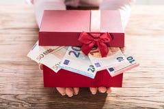 Contenitore di regalo della tenuta della donna di noi euro fatture Immagine Stock Libera da Diritti