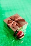 Contenitore di regalo di Brown e palla di Natale su fondo verde, primo piano Fotografia Stock