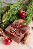 Contenitore di regalo di Brown, palla di Natale e rami verdi dell'abete Fotografia Stock