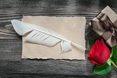 Contenitore di regalo di carta d'annata della rosa rossa della piuma dello strato sul bordo di legno uff Immagini Stock