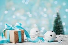 Contenitore di regalo di Natale, campana di tintinnio ed albero di abete vago contro il fondo blu del bokeh Cartolina d'auguri di Fotografia Stock
