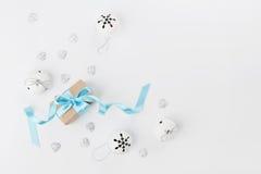 Contenitore di regalo di Natale con il nastro blu e campana di tintinnio su fondo bianco da sopra Cartolina d'auguri di festa Mod Fotografia Stock