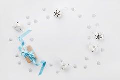 Contenitore di regalo di Natale con il nastro blu e campana di tintinnio sulla tavola bianca da sopra Cartolina d'auguri di festa Fotografia Stock