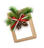 Contenitore di regalo di Natale con l'arco del nastro, il ramoscello dell'abete, i coni e la corrente alternata Immagini Stock