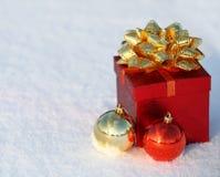 Contenitore di regalo di Natale con le palle brillanti su neve. Fuori. Immagine Stock
