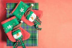 Contenitore di regalo di Natale a fondo rosso con i calzini per il presente Fotografie Stock