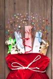 Contenitore di regalo di Santa Claus Bag Full By Present, sacco rosso di Natale sul vecchio fondo di legno della parete fotografia stock libera da diritti