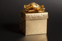 Contenitore di regalo dorato con il nastro dorato fotografia stock