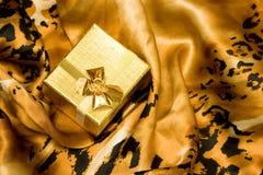 Contenitore di regalo dorato su seta fotografia stock