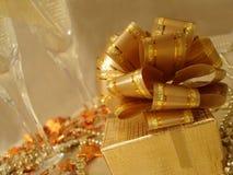 Contenitore di regalo dorato su una bella priorità bassa con i vetri del champagne Fotografia Stock Libera da Diritti