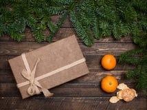 Contenitore di regalo e mandarini con i rami dell'abete su backg di legno rustico Fotografia Stock