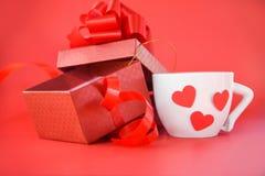 Contenitore di regalo e tazza di caffè macchiato aperti con il giorno di biglietti di S. Valentino rosso del cuore su fondo rosso immagine stock libera da diritti