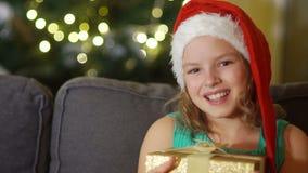 Contenitore di regalo felice di Natale di apertura del bambino Il bambino divertente si è vestito in cappello di Santa Claus in c archivi video