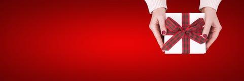 Contenitore di regalo isolato su fondo rosso Presente della tenuta della donna Immagine Stock Libera da Diritti