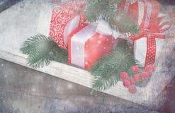 Contenitore di regalo legato con un nastro rosso, i rami dell'abete, la caramella e il christm Fotografie Stock
