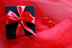Contenitore di regalo nero con il nastro rosso sul color scarlatto del tessuto trasparente Immagine Stock Libera da Diritti