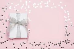 Contenitore di regalo piacevole con l'arco su fondo rosa con le stelle d'argento Copyspace Spazio libero per il vostro testo Vist Fotografie Stock Libere da Diritti