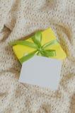 Contenitore di regalo Presenti con la cartolina vuota sul fondo della coperta Knitted fotografia stock libera da diritti