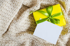 Contenitore di regalo Presenti con la cartolina vuota sul fondo della coperta Knitted immagini stock