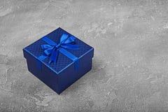 Contenitore di regalo quadrato blu scuro con l'arco brillante del raso Fotografie Stock