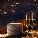 Contenitore di regalo radiante luminoso con champagne ed il fondo del bokeh Fotografie Stock