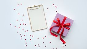 Contenitore di regalo rosa con l'arco rosso del nastro Festa presente Isolato su priorità bassa bianca immagini stock libere da diritti