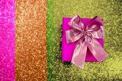 Contenitore di regalo rosa con un arco su un fondo scintillante di colore fotografia stock