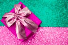 Contenitore di regalo rosa con un arco su un fondo scintillante di colore fotografie stock libere da diritti