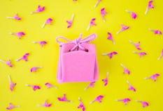 Contenitore di regalo rosa su un fondo giallo con i fiori Concetto festivo Disposizione piana, vista superiore fotografia stock libera da diritti