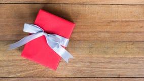Contenitore di regalo rosso con il nastro bianco sul fondo di legno della tavola dalla vista superiore con lo spazio della copia Immagini Stock Libere da Diritti