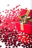 Contenitore di regalo rosso con l'arco dorato e molti piccoli cuori rossi su bianco fotografia stock libera da diritti
