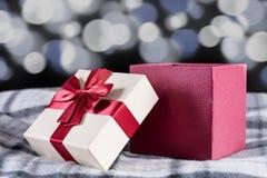 Contenitore di regalo rosso con l'arco sul retro scrittorio ed albero di Natale di legno immagini stock