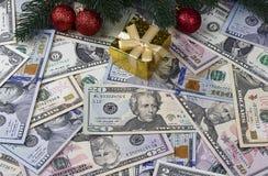 Contenitore di regalo rosso delle palle dei rami di pino di natale del fondo del dollaro Immagine Stock