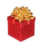 Contenitore di regalo rosso di Natale con l'arco del nastro dell'oro, isolato Immagine Stock