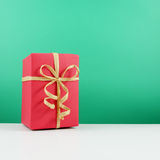 Contenitore di regalo rosso di Natale con l'arco del nastro della carta marrone Fotografie Stock Libere da Diritti