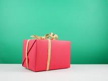 Contenitore di regalo rosso di Natale con l'arco del nastro della carta marrone Fotografia Stock