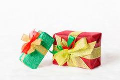 Contenitore di regalo rosso e verde di Natale con il nastro dorato brillante Immagini Stock