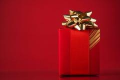 Contenitore di regalo rosso su fondo rosso con spazio per testo Carta di Buon Natale Immagine Stock
