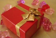 Contenitore di regalo rosso su una bella priorità bassa dorata Fotografie Stock
