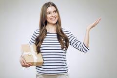 Contenitore di regalo sorridente della tenuta della donna che presenta mano vuota Fotografia Stock