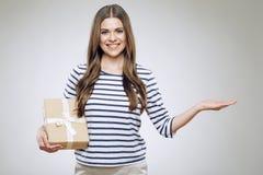 Contenitore di regalo sorridente della tenuta della donna che presenta mano vuota Fotografie Stock