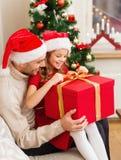 Contenitore di regalo sorridente di apertura della figlia e del padre Immagine Stock Libera da Diritti