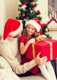 Contenitore di regalo sorridente di apertura della figlia e del padre Fotografie Stock Libere da Diritti
